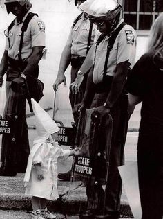 During a Ku Klux Klan rally in Georgia, Todd Robertson, a photographer for The Gainsnville Times, was sent to capture the moment. There were 66 Klan members and three officers at the rally with about 100 onlookers.  Robertson followed a mother and her children. Her two young boys were dressed in the Klan robes with the pointy white hats. To Robertson's shock, one of the boys went up to an African An American officer and looked into his shield. Before his mother could snatch him away,
