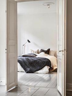 parquet blanc, un sol blanc laqué, grande porte claire et lit