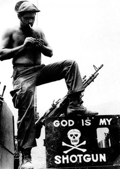 Khe Sanh, South Vietnam, April 12, 1971 - An American soldier, lighting a cigarette in front of his machine gun atop a vehicle, stands above a sign serving as testament to his battlefield beliefs.