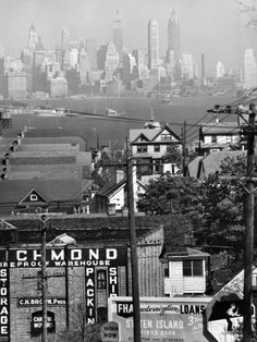 NYC. Lower Manhattan and Ferry Docks  over the Rooftops in Staten Island // Andreas Feininger