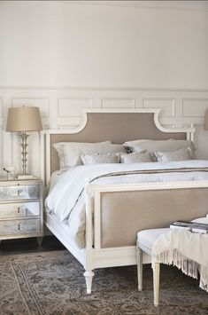 A bedroom should always feel inviting and comfortable. Here, the designer combined beautiful upholstered pieces with mirrored ones. The result is a room that feels feminine and elegant.    Bed is by Hickory White and bedside table is by Lillian August.
