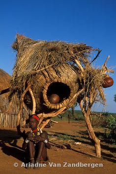 ETHIOPIA, Turmi, Hamer village, Hamer girl sitting at a granary, the Hamer are nomadic pastoralists