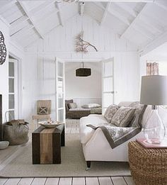 Even with the lack of beachy accessories, this room still has that distinctly beachy vibe. It feels so open and airy, with the panels and mixture of furniture adding to that ambiance. #beachhouse #white