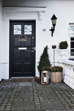 studio karin: Exteriör FASAD o ENTRÉ. Black classic door, entrance, facade, hurricane lamp, wicker, white fence