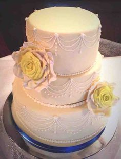 Cream and lemon three tier Wedding Cake with elegant royal icing piped swags and yellow rose details