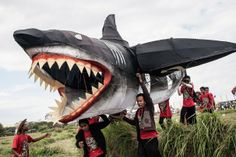 Participants carry a shark-shaped kite during the Bali Kite Festival in Denpasar, Indonesia. The event is a seasonal religious festival, which is intended to send a message to Hindu gods to create abundant harvests and crops. More than 1,100 kites are flown during the three-day festival. Photo: Putu Sayoga / Getty Images
