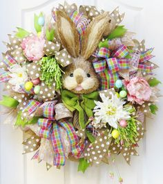 Easter Wreath, Bunny Wreath, Deco Mesh Easter Wreath, Burlap Easter Wreath, Rabbit Face, Mesh Spring Wreath, Easter Decor, Door Wreath  Delight your door or mantle with this sweet Easter Bunny Wreath. The base is handcrafted with plush mesh ribbon loops in a natural color. Soft pink deco mesh is woven throughout. This Easter bunny wreath is generously filled with several different patterns of premium ribbon streamers which include a spring plaid, lime denim, natural and white polka dot, and…