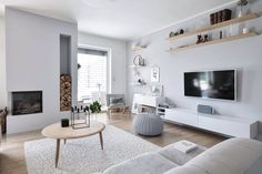 Bright whites, neutral greys and light, natural wood accents make this living room a calming sanctuary. Practical elements like the log storage nook and floating shelving units help keep it functional and organized. Condo Living Room, Living Room Accents, Living Room White, White Rooms, Living Room Decor, Interior Design Inspiration, Home Interior Design, Hygge Home, Wood Accents