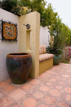 Summer style! Outdoor garden water fountain in a large ceramic planter pot or jar - creating a water feature surrounded by gardens! Mediterranean style! Love the tile patio and the stone wall! #largegardenfountains