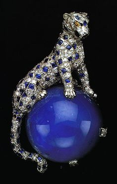 In 1949, the Duchess of Windsor acquired this diamond and sapphire panther pin from Cartier. The panther is crouched in a life like pose on a large perfect round cabochon star sapphire weighing 152.35 carats.