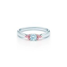 Tiffany & Co. pink diamond engagement ring featuring a round brilliant white diamond elegantly framed by six Fancy Pink diamonds.