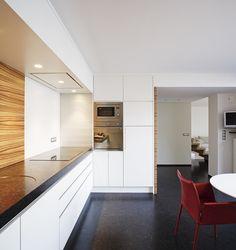 Moderne keuken met werkblad in blauwsteen, houten spatwand en rode stoelen als eyecatcher - ontwerp van Frank Sinnaeve en keukenblad van Potier Stone