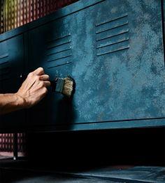 Eine Hand betupft einen Metallschrank mit brauner Farbe.