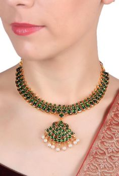 A big peacock feather shaped pendant with dangling pearls and green kemp studded stones. This ethnic piece will look with any Indian outfit. Dimension: L: 6.5 inch Weight: 54 gm Color: Golden, green & white Material: Gold plated brass Closure: Adjustable Finish: Hand-crafted Inspiration: Bharatnatyam Jewelry