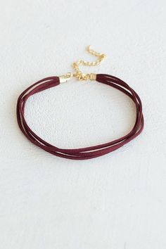 """Simple, yet stylish. Get your boho on in this burgundy triple layered suede lace choker! Wear along or layer with your other favorite necklaces! 12"""" long plus 4"""" chain extender"""