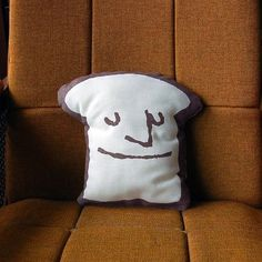 Moody Toast Pillow: This moody toast pillow makes me smile (he's grumpy on the other side). I would like to give him a home on my Eames shell chair.