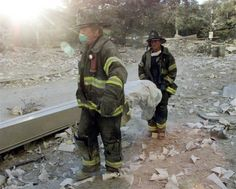 """Firefighters carry a body from the World Trade Center aftera terrorist attack September 11, 2001. Two hijacked commercial planes slammed into the twin towers of the World Trade Center Tuesday, causing both 110-story landmarks to collapse in thunderous clouds of fire and smoke and killing a """"tremendous number."""" of people. (Credit: © Peter Morgan / Reuters)"""