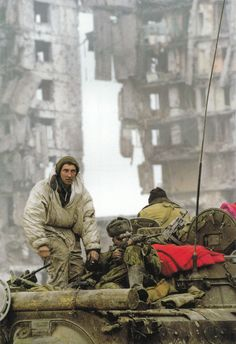 A Russian sniper takes aim with a assistance of a tank commander in a Battle of Grozny. First Chechen War, 1994.
