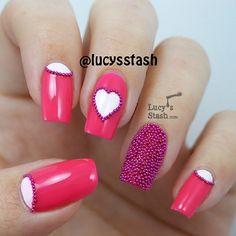 Uñas en rosa fucsia adornadas con micro perlas moradas, lunas en blanco y un corazón - Uñas Pasión