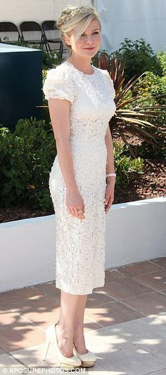 Kirsten Dunst looks ultra-feminine in a whimsical white Dolce & Gabbana dress, bejeweled headband, and gold and white platform pump!