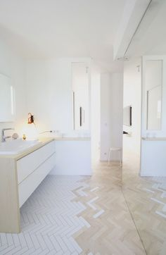 White ceramic tiles creating parquet effect with timber parquet flooring.