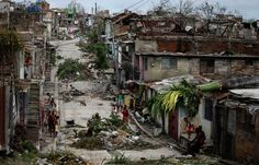 People walk on a street littered with debris after Hurricane Sandy hit Santiago de Cuba on Oct. 26. The Cuban government said on Thursday night that 11 people died when the storm barrelled across the island, most killed by falling trees or in building collapses in Santiago de Cuba province and neighboring Guantanamo province. (Desmond Boylan/Reuters)