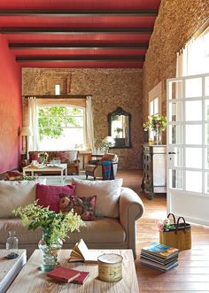 Usar varias texturas es un recurso para dar calidez a un salón rústico. La decoradora Marta Esteve combinó ladrillo, piedra y madera, añnadió tonos caldera y flores frescas.