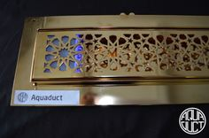 Gold plated Moresque linear drain by Aquaduct.  www.aquaduct.co