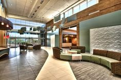 The two-story atrium features natural light, comfortable seating, and private client consult rooms. Photographer: Dustin Revella