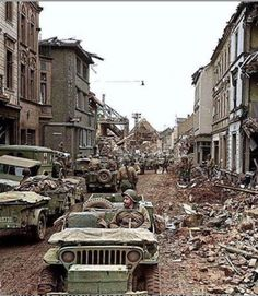 U.S. Army soldiers accompanied by Willys MB Jeeps from the 407th Infantry Regiment, 102nd Infantry Division, of the U.S. Ninth Army move down Kölner Strasse street in the destroyed town of Erkelenz, Germany, in March 1945.