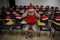 """A student of the """"Escola de Papai Noel do Brasil"""" (Brazil's school of Santa Claus) wears his hat before lessons in Rio de Janeiro. Lessons include singing, how to dress, and how to care for their beards."""
