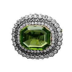 1890s Peridot and Diamond Brooch. An impressive Napoleon III brooch, the principal stone a 37.5 ct peridot surrounded by three graduating rows of old-cut diamonds weighing a total of 13.5 cts (approx), set in silver on gold. Circa 1890, with French import marks.
