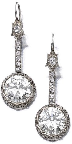Pair of diamond earrings.      Each suspending a brilliant-cut diamond weighing respectively 5.05 and 5.51 carats, surmounted by a line of circular-cut stones. Sotheby's.