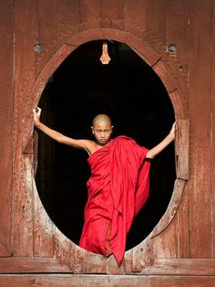 Photo: A boy in robes looking out from a monastery