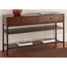 The Hammond sofa table features a casual style that will easily blend with any dacor. With its beautiful medium cherry finish and rustic metal finished base, this sofa table offers two spacious drawers with antique copper finished knobs.