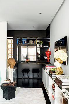 Integrada à sala e bem reduzida, tembancada americana, com fruteira Alessi. Sobre o rack da sala, escultura de cabeça em vaso Fornasetti Vintage 70's, com arranjo de Nelson Quionha