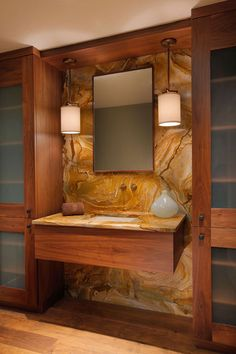 There's nothing like a beautiful stone slab to make a vanity a showstopper. The minimalist wood cabinet topped with the same stone allows the stone to take center stage.