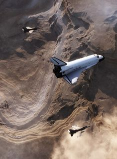 Two Falcons escorting Space Shuttle Discovery on re-entry.