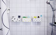 Three IKEA STUGVIK baskets in the shower, holding shampoo and other bath products