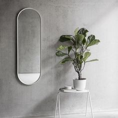 An oval wall mirror with a black powder coated frame. Designed as part of a bathroom series by Norm Architects for Menu.