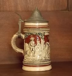 """Small German Beer Stein with Lid. Appears to be vintage. Has """"Germany"""" and """"11"""" stamped on the bottom. Size is about 5"""" high (with lid closed). Very decorative and unique piece. There are a few very s"""