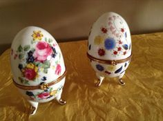 Duas pequenas caixas de porcelana repres. ovos, decoração floral com metal dourado med. 10 cm.