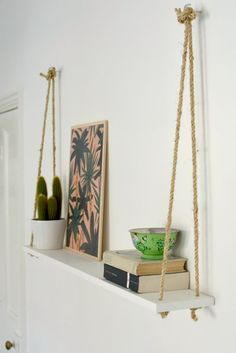 Just three ingredients (rope, two hooks and a painted shelf) are all it takes to construct this easy DIY rope shelf.