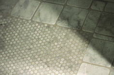 "Shower floor of carrara penny rounds from Mission Stone & Tile with a border of 4""x4"" tumbled carrara tile."