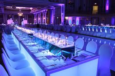Long, illuminated tables held rectangular vases wrapped in the Diffa logo and…