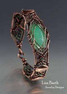 Here is a hand woven bracelet I made with copper wire and a green Varisite cab. --Lisa Barth