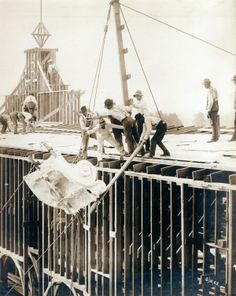 Workers hoisting the first piece of staff onto the Palace of Varied Industries during the construction phase for the 1904 World's Fair, 10 June 1902. Missouri History Museum