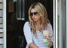 Celebrities are creatures of habit just like the rest of us.  So it's no wonder that Ashley Tisdale was, once again, spotted grabbing in icy coffee drink at her local Coffee Bean and Tea Leaf café that dawn (July 16).  The High School Musical hottie sauntered out to her car, carrying her beverage and sporting a white-with-black-stripes shirt, designer jeans, and a pair of high heels.