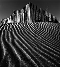 Beach, fence, sand, shadows and light. B photography.