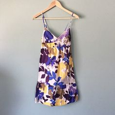 """American Eagle Floral Sundress American Eagle Floral Spaghetti Strap Empire Waist 100% cotton sundress // Colors are lilac, royal purple, royal blue, butter yellow, gray, tan, white // decorative trim along triangle top bust // elastic cutout  back with tie string // adjustable straps // ruffle detailing along bottom hem //  100% cotton lining // perfect for spring or summer!! // sz 2 // 13"""" waist / 29"""" length from top of bust //  20% off 3+ Bundles // 3.26.23 No trades American Eagle…"""